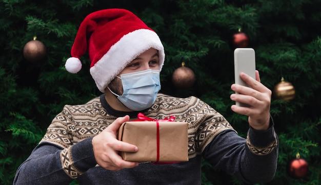Parabéns online de natal. retrato de homem usando chapéu de papai noel e máscara médica, dando uma caixa de presente com fita vermelha, bokeh de árvore de natal no fundo