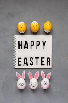 Parabéns pela páscoa e ovos de páscoa decorados como coelhos e filhotes em fundo cinza.