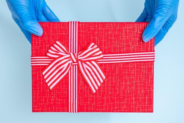 Parabéns pelo feriado durante a pandemia do coronavírus. mãos com luvas médicas azuis seguram uma caixa de presente vermelha com uma fita isolada na mesa azul clara, copie o espaço