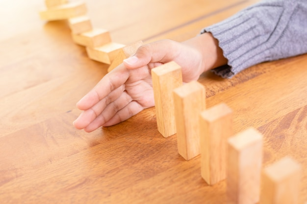 Parada de mão em bloco de madeira, criando um efeito de risco de dominó
