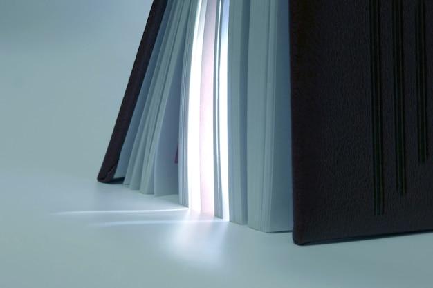 Parado entreaberto no final do livro com o produto de sua luz. o livro é uma fonte de conhecimento