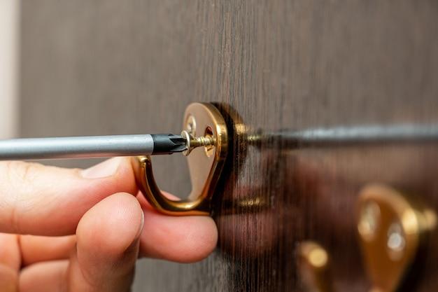 Parafusar o gancho para roupas na parede do guarda-roupa com uma chave de fenda