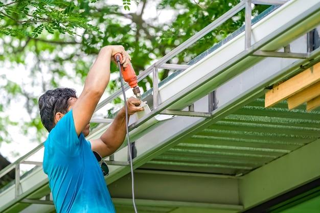 Parafuso do trabalhador asiático, chave de fenda para criar e reparar o ralo de água do telhado.