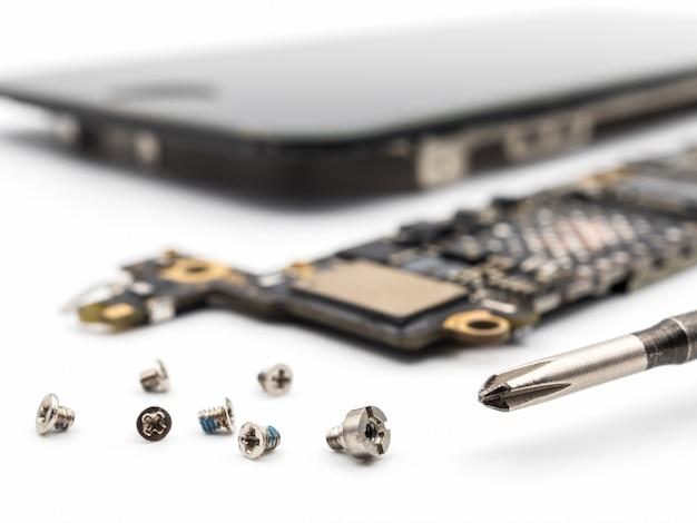 Parafuso e chave de fenda com componentes do smartphone turva