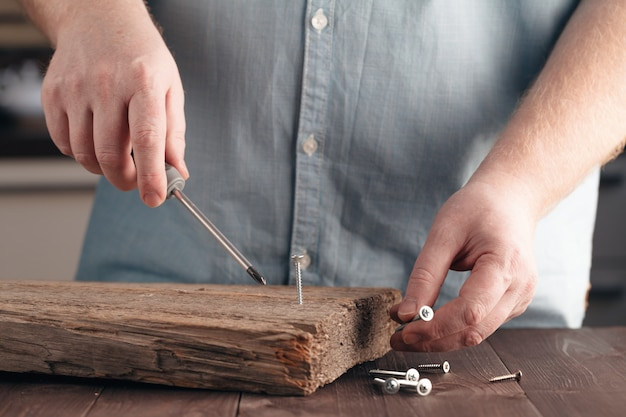 Parafuso sendo parafusado em um pedaço de madeira