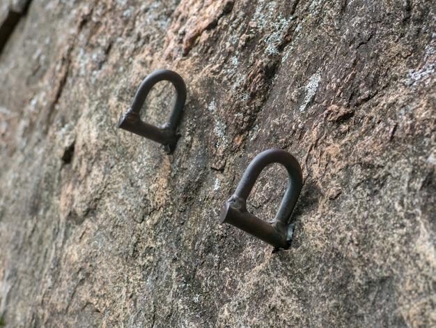 Parafusos de escalada em uma parede de rocha íngreme