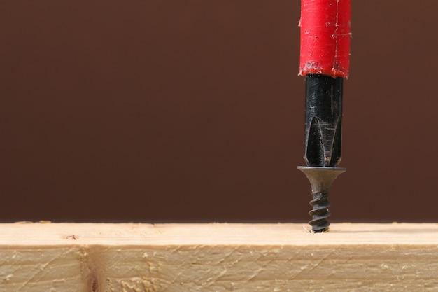 Parafusos de ferro preto aparafusados à madeira com uma chave de fenda.