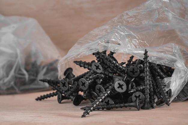 Parafusos de madeira pretos pilha pilha em saco plástico no fundo de madeira