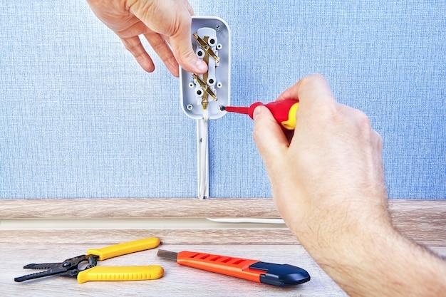 Parafusos de torção dentro da tomada de parede com chave de fenda, trabalho de fiação elétrica.