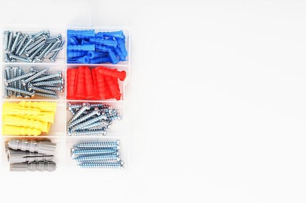 Parafusos e buchas de vários tamanhos, tipos e cores em uma caixa de plástico transparente. a vista do topo