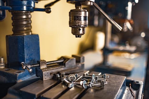 Parafusos e porcas de metal cromado em uma máquina de perfuração no local de trabalho de um chaveiro