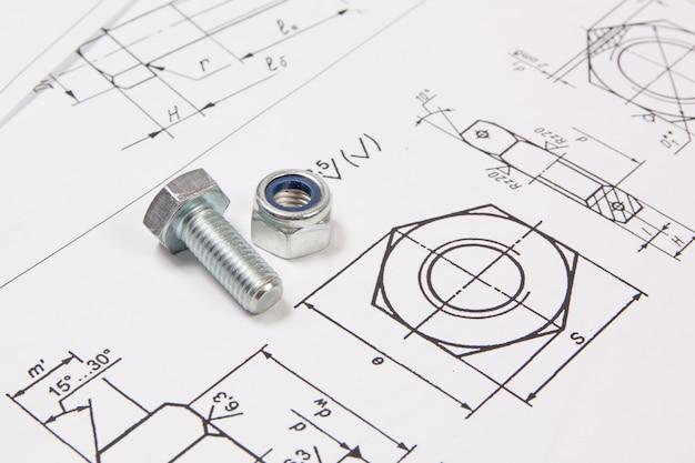 Parafusos e porcas sobre desenhos de engenharia.