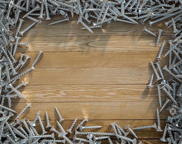 Parafusos formando uma moldura em torno de uma superfície de madeira