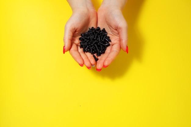 Parafusos nas mãos de uma menina, vista de cima em close-up, isolado