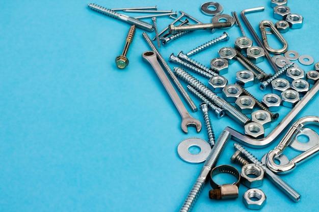 Parafusos, porcas, chaves e outras ferramentas de construção em uma superfície azul