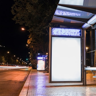 Paragem de autocarro com outdoor de publicidade em branco perto da rua na cidade
