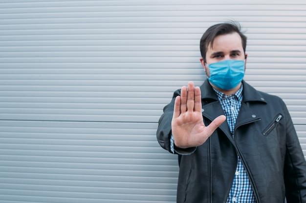 Paragem de gesto apresentando homem. homem usa máscara protetora contra doenças infecciosas e gripe. conceito de cuidados de saúde. quarentena do coronavírus.