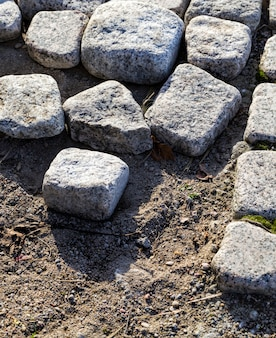 Paralelepípedos cúbicos quadrados a partir dos quais o pavimento é construído, close do local de construção durante a construção ou reconstrução