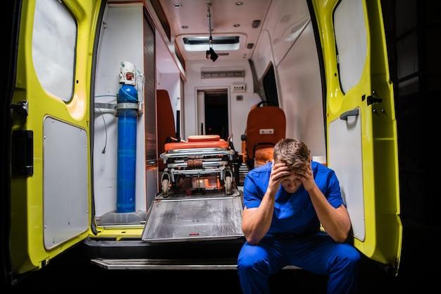 Paramédico confuso em um uniforme azul, sentado na traseira de um carro de ambulância