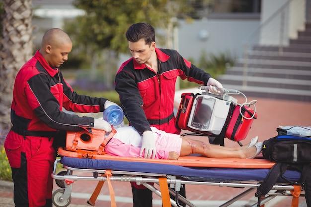 Paramédico dando oxigênio à garota ferida