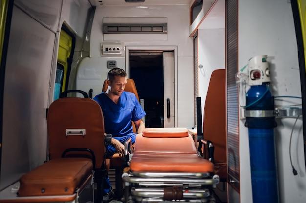 Paramédico de uniforme sentado no carro da ambulância
