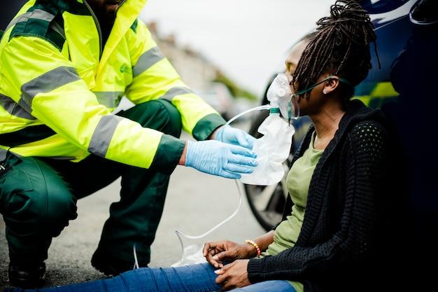 Paramédico do sexo masculino colocando máscara de oxigênio para uma mulher ferida em uma estrada