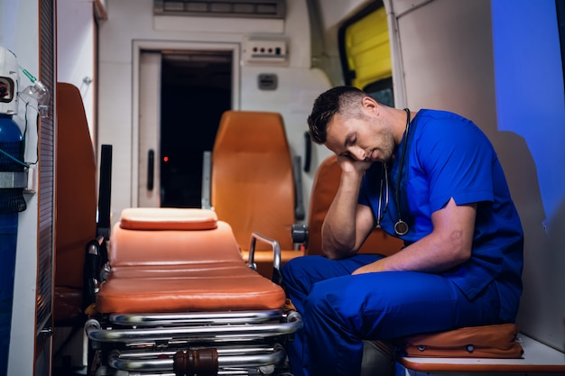 Paramédico exausto dormindo em um carro de ambulância