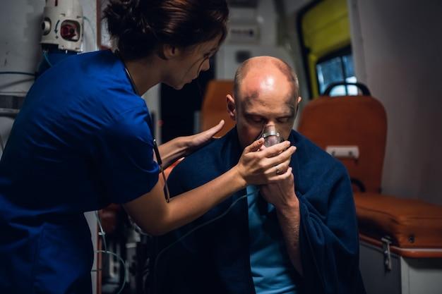 Paramédico pressionando uma máscara de oxigênio no rosto de um homem ferido