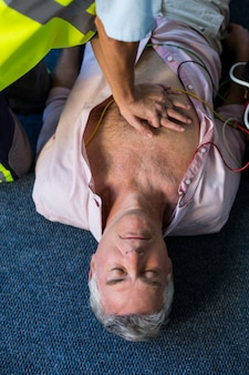 Paramédico usando desfibrilador externo durante ressuscitação cardiopulmonar