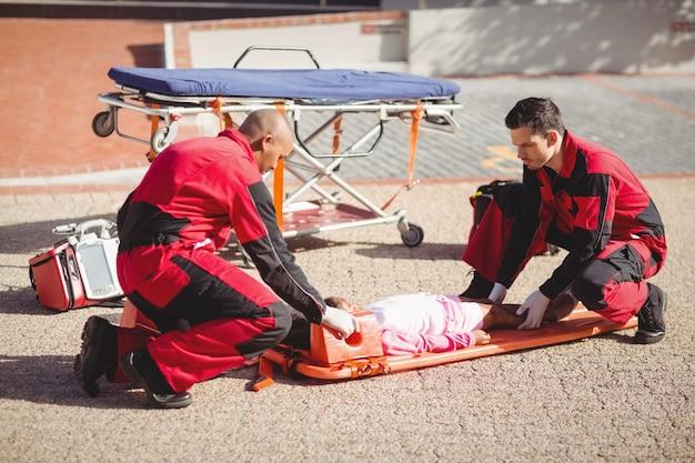 Paramédicos colocando garota ferida em uma tabela