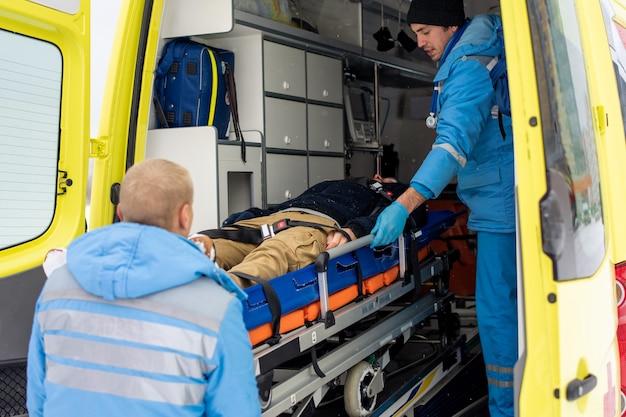 Paramédicos de uniforme empurrando maca com homem inconsciente fixo para dentro da ambulância para levá-lo ao hospital