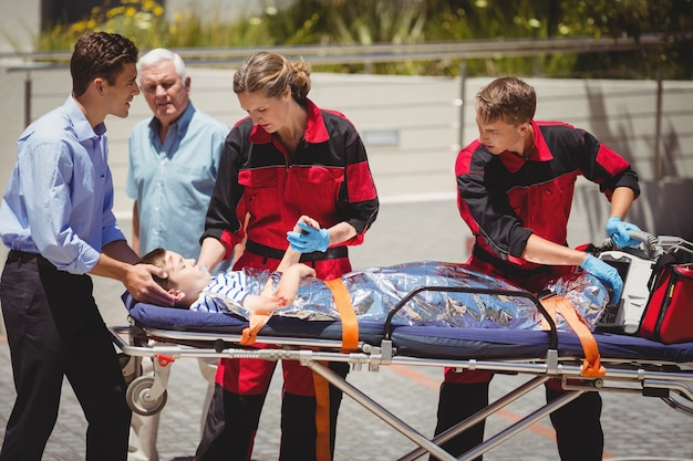 Paramédicos examinando menino ferido
