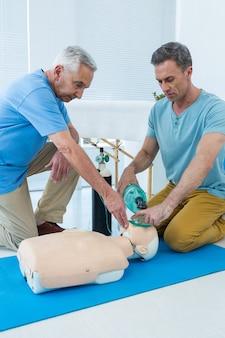 Paramédicos praticando ressuscitação cardiopulmonar em manequim