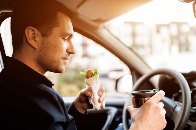 Parando para comer algo. homem comer lanche no carro e bebe café ou chá.