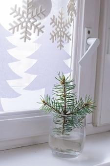 Parapeito da janela da decoração de natal. galho de árvore do abeto em vidro.