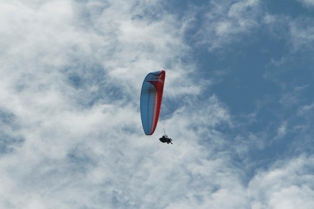 Parapente à distância voando com 2 pessoas entre as nuvens e o céu azul