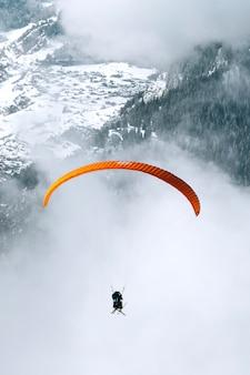 Parapente em dia nublado pela montanha