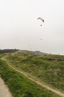Parapente nas falésias verdes em dia nublado