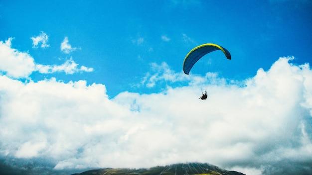 Parapente. parapente em um céu azul e fundo de montanha kazbek.