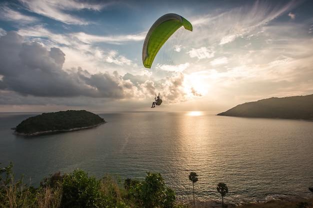 Parapente perseguindo o pôr do sol no ponto de vista do moinho de vento. phuket, tailândia.