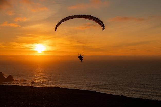 Parapente que voa sobre a costa do mar no por do sol. esporte de parapente