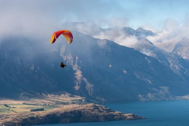 Parapente sobre o lago e a grande montanha de manhã