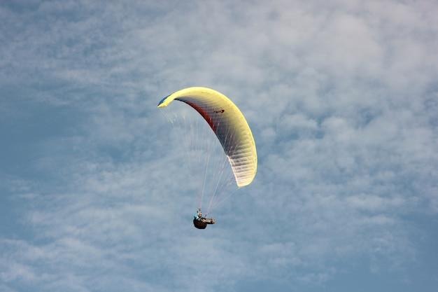 Parapente voando em um paraquedas contra um céu azul com nuvens