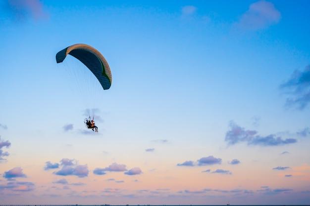 Parapente voando no céu ao pôr do sol