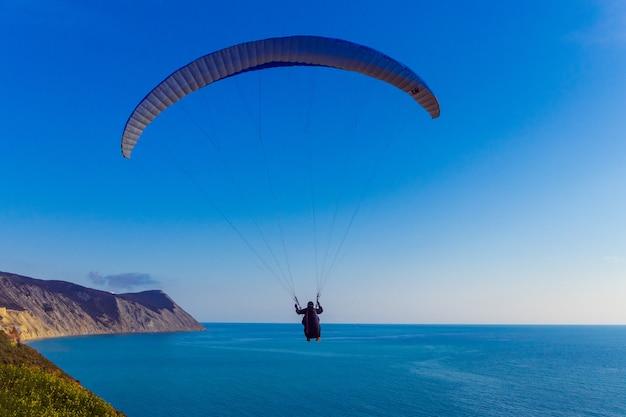 Parapente voando sobre a costa rochosa do mar negro perto da cidade de anapa