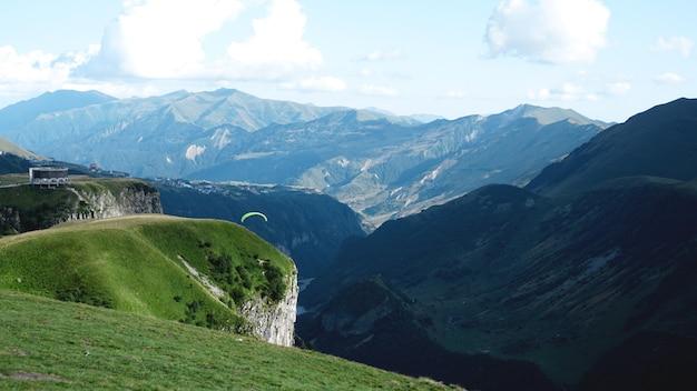 Parapente voando sobre montanhas durante o dia de verão - geórgia, kazbegi
