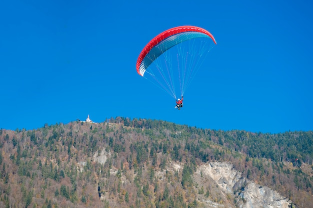 Parapentes voando com um paramotors com bela vista para a montanha contra o céu azul