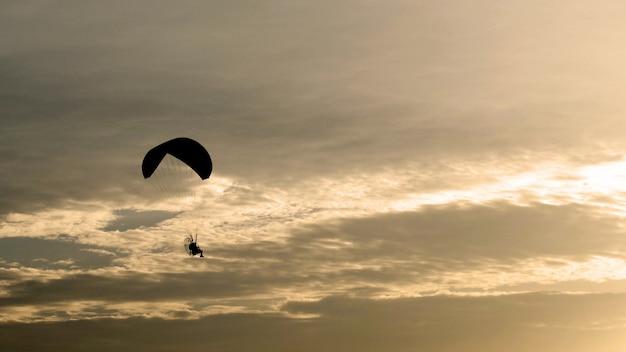 Paraquedas ou paramotor voar no pôr do sol, sombra negra, atividade esportiva