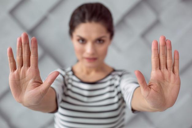 Parar a violencia. foco seletivo das mãos de uma mulher bonita e atraente enquanto diz pare com a violência