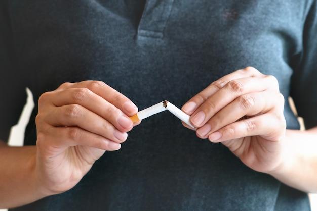 Parar de fumar, sem dia de tabaco, mãos de mulher quebrando o cigarro